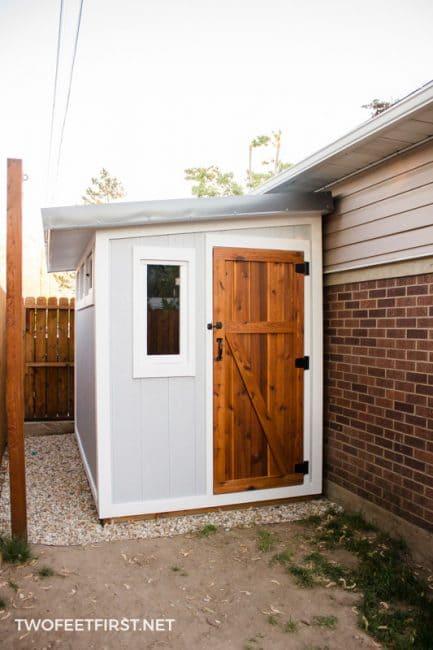 grey siding DIY shed with cedar door