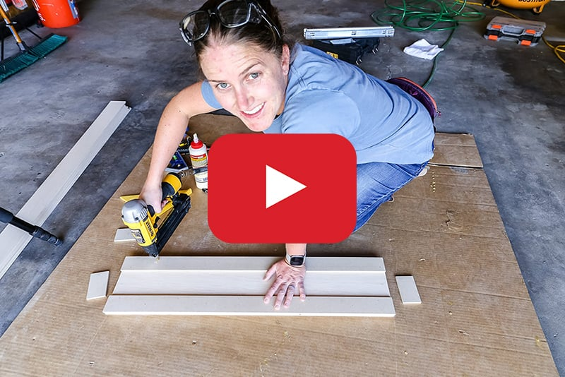 woman adding trim to kitchen cabinets with play button