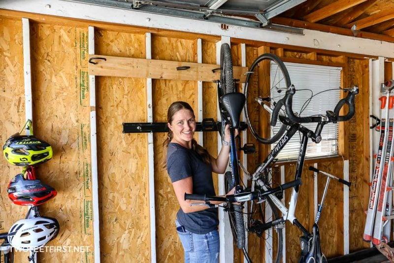 woman removing bike from garage bike rack