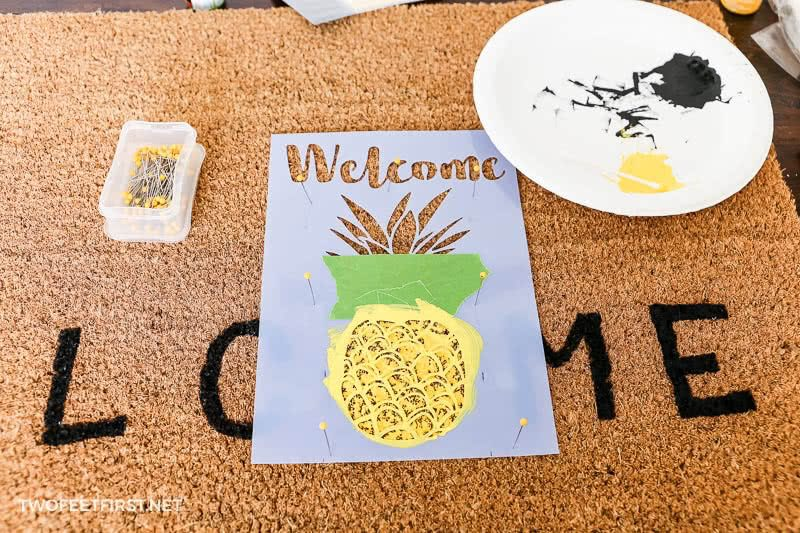painting pineapple onto doormat