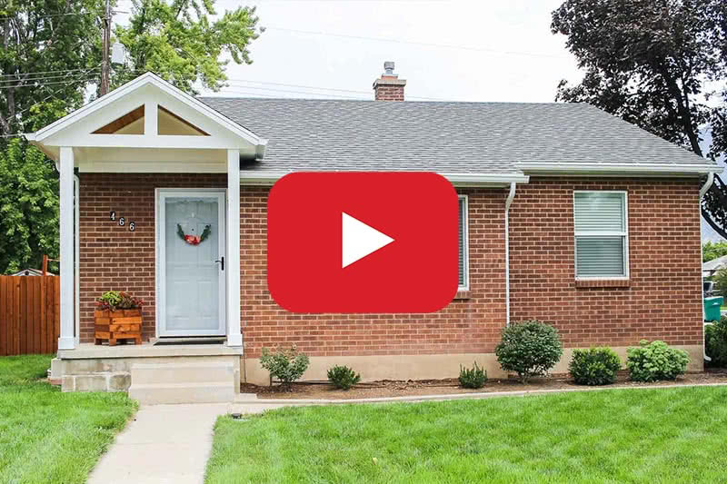 red brick home with front porch and video playing icon for youtube