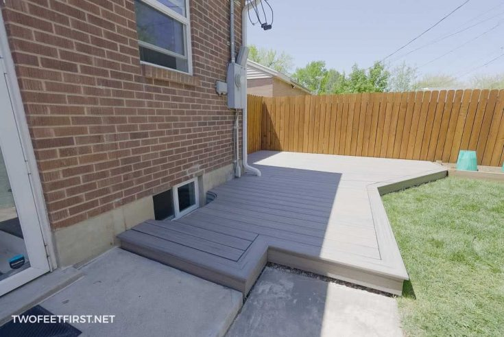 grey floating deck next to home and fence