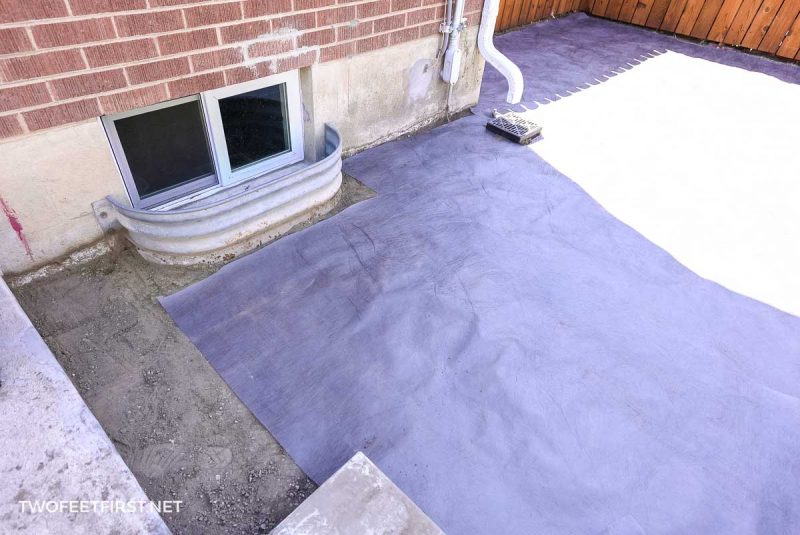 placing fabric weed barrier for floating deck foundation