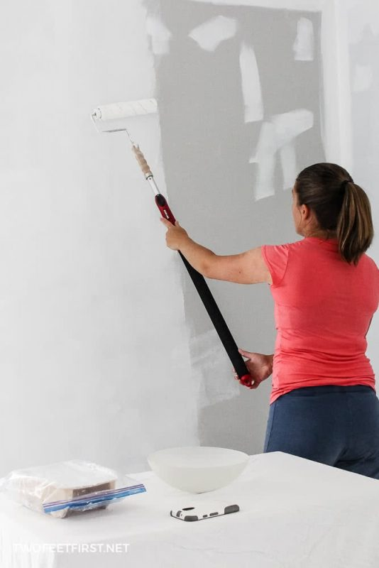 rolling paint onto the wall