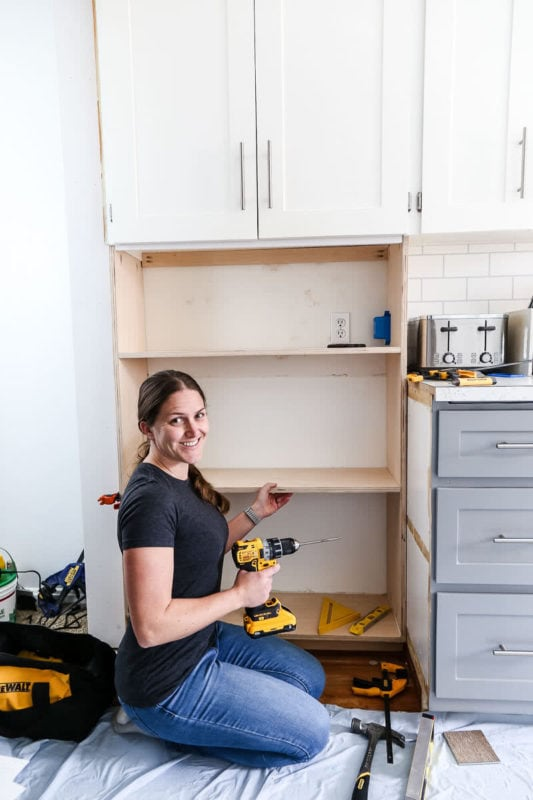 women building cabinet in kitchen