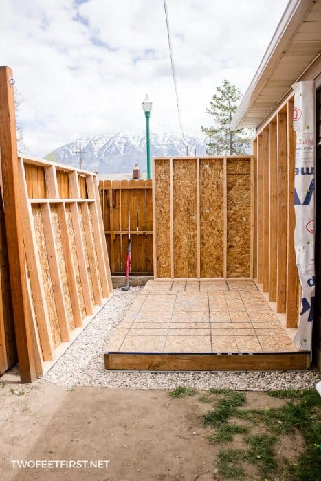 two shed walls attached to shed floor with one wall waiting to be installed