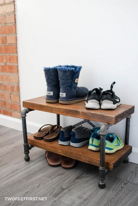industrial shoe rack made from wood and metal pipe with shoes sitting on it