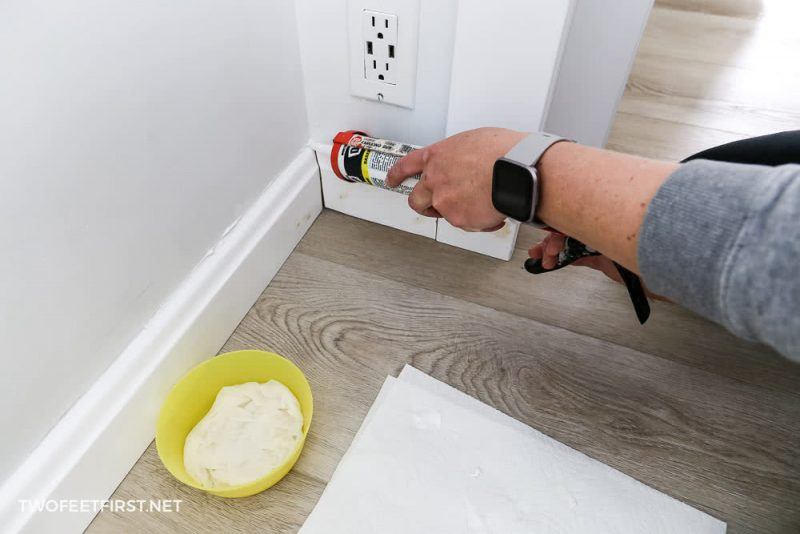 applying caulk to baseboard