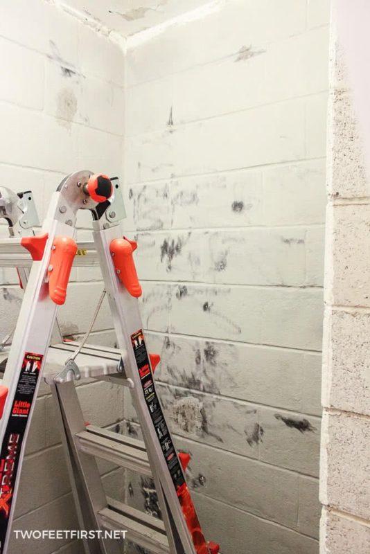 ladder in room scraping cinder block
