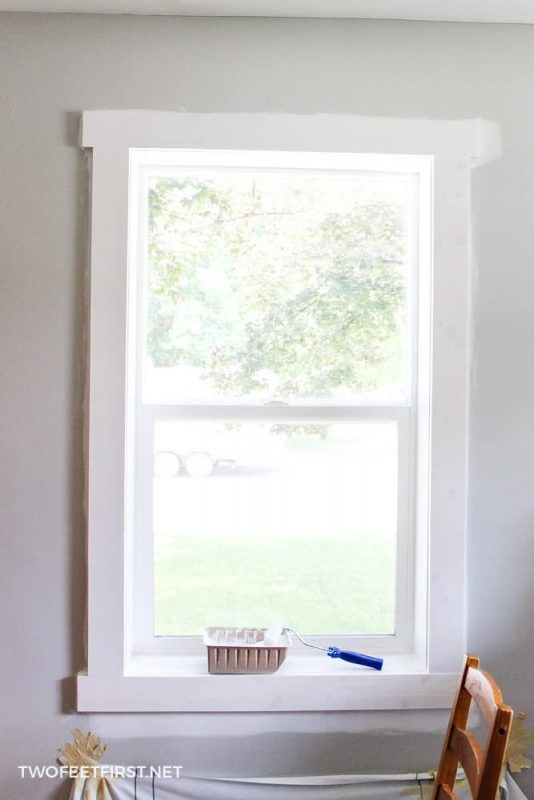 using a roller to paint window casing
